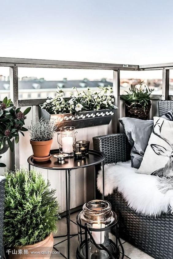 26-lots-of-pots-with-greenery-a-wicker-chair-a-coffee-table-and-a-large-candle-lantern-for-coziness.jpg