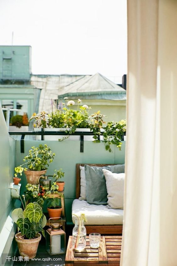 24-a-very-small-balcony-with-a-wooden-crate-as-a-table-an-upholstered-bench-a-ladder-and-lots-of-potted-greenery.jpg
