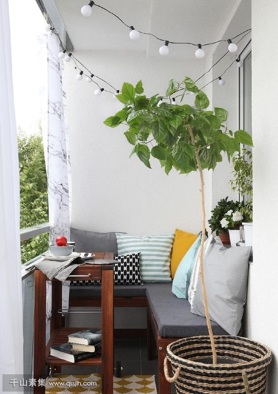 21-a-small-cozy-balcony-with-an-L-shaped-upholstered-bench-a-small-coffee-table-and-potted-plants.jpg