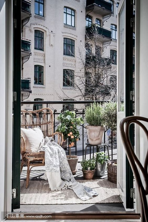 20-a-small-balcony-with-a-wicker-chair-potted-greenery-and-baskets-for-storage.jpg