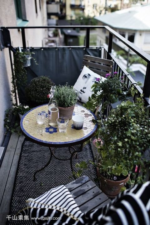 19-a-monochromatic-balcony-with-chairs-and-a-lot-of-potted-greenery-is-spruced-up-with-a-colorful-mosaiic-table.jpg