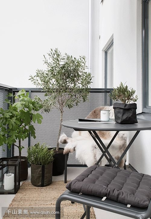 17-a-dark-metal-folding-furniture-set-potted-greenery-and-flowers-candle-lanterns-for-a-Scandinavian-feel.jpg