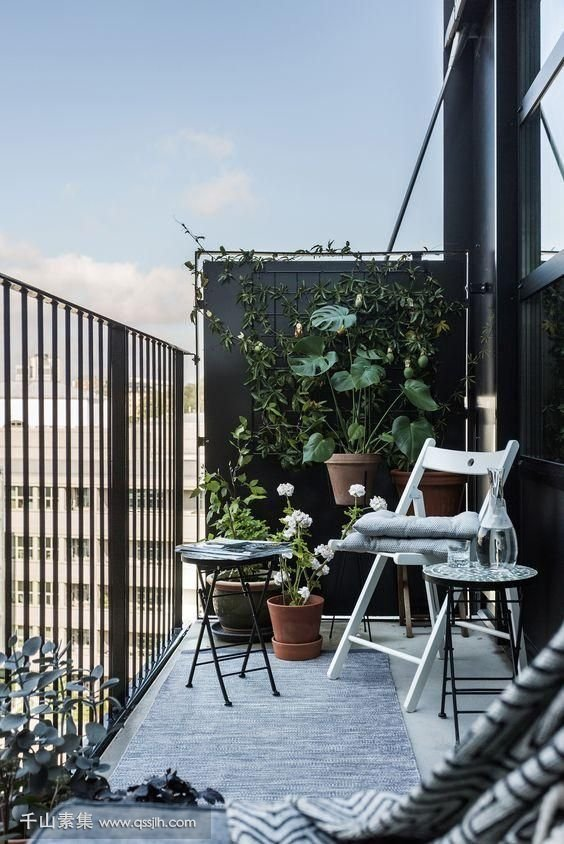 16-a-black-balcony-done-with-a-couple-of-folding-chairs-and-a-small-coffee-table-plus-a-lot-of-greenery-around.jpg