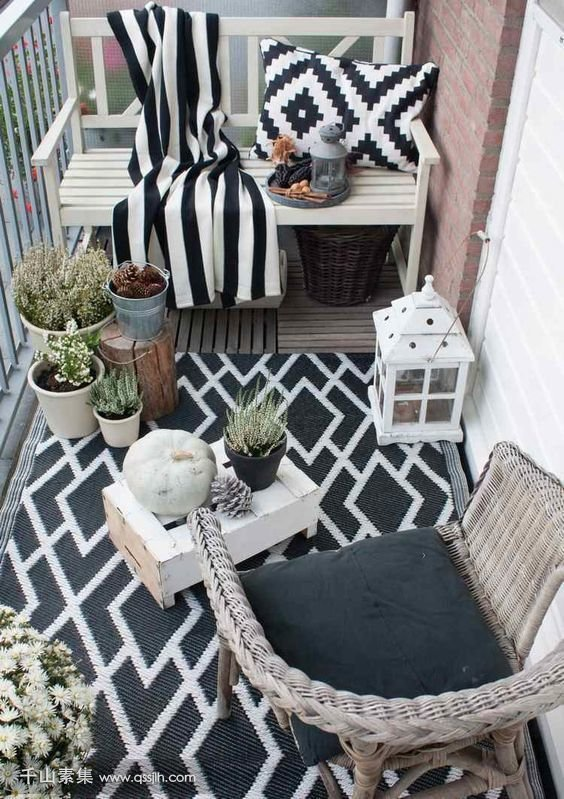 11-a-monochromatic-balcony-with-wicker-and-wooden-furniture-black-and-white-textiles-potted-plants-and-candle-lanterns.jpg
