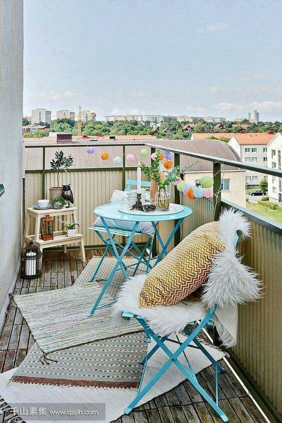 04-a-colorful-balcony-with-bright-blue-furniture-a-ladder-candle-lanterns-and-rugs.jpg