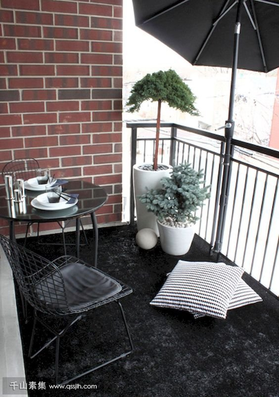 03-a-black-rug-a-metal-dining-set-potted-plants-and-a-large-umbrella-for-privacy-and-to-protect-from-the-sun.jpg