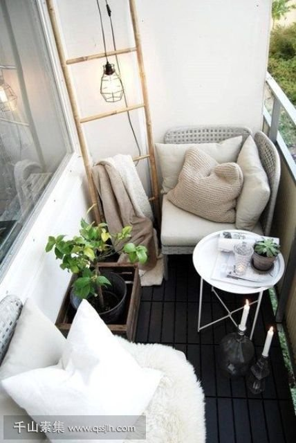 02-a-black-and-white-balcony-with-two-cofy-wicker-seats-a-coffee-table-candles-and-a-ladder-for-storage.jpg