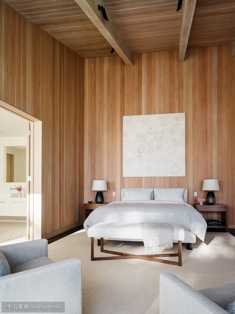 08-The-master-bedroom-features-comfortable-contemporary-furniture-and-much-wood-that-clads-the-walls-and-a-high-ceiling.jpg