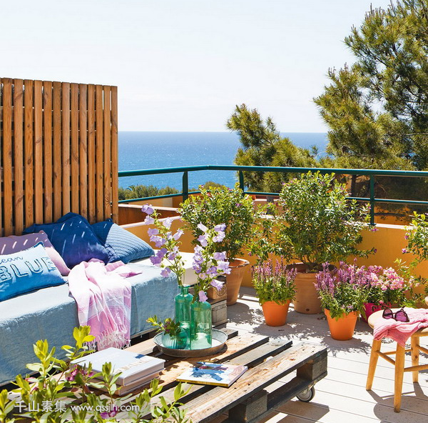 06-The-terrace-is-decorated-with-some-stools-a-pallet-table-a-daybed-and-lots-of-potted-flowers-and-greenery.png