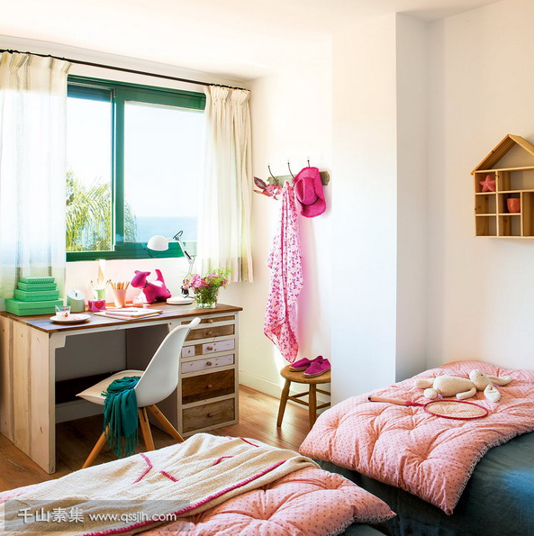 05-The-kids-room-is-done-with-bold-green-and-pink-theres-a-large-window-to-bring-light-in-and-two-beds.png